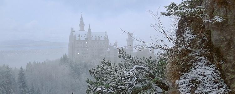 Sleepy Neuschwanstein Castle in fog and snow. Bavaria, Germany.