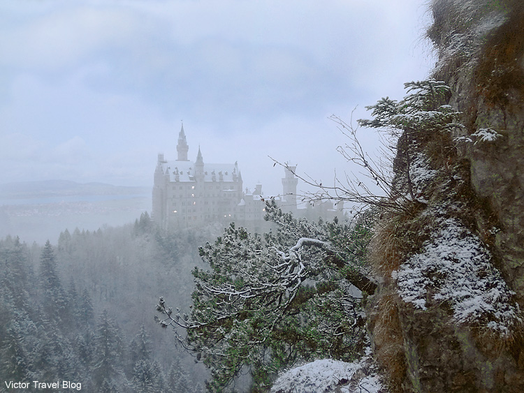 Early morning. Sleepy Neuschwanstein Castle in fog and snow. Bavaria, Germany.