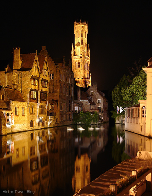 A canal in Bruges with the famous Belfry tower.