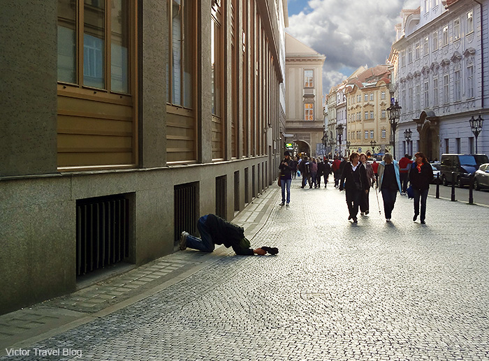 Kneeling men on the street of Prague, Czech Republic.