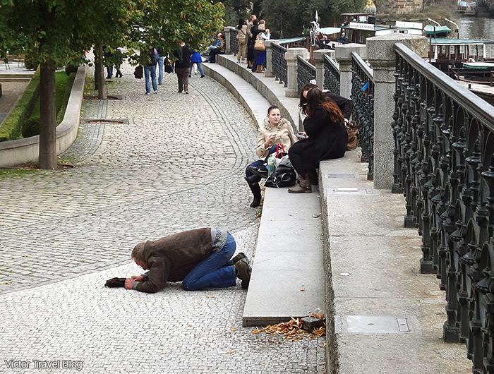 Kneeling men on the street of Prague, Czech Republic.